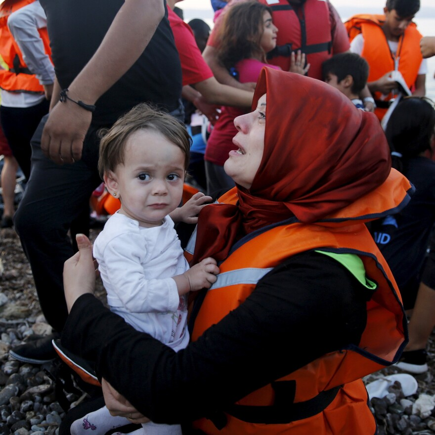 Syrian refugee woman cries by one of her children as she and family members arrive in an overcrowded dinghy on the Greek island of Lesbos after crossing a part of the Aegean Sea from the Turkish coast, on Saturday.