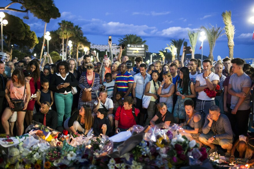 People gather at a makeshift memorial to honor the victims of an attack on Friday, near the area where a truck mowed through revelers in Nice, France.