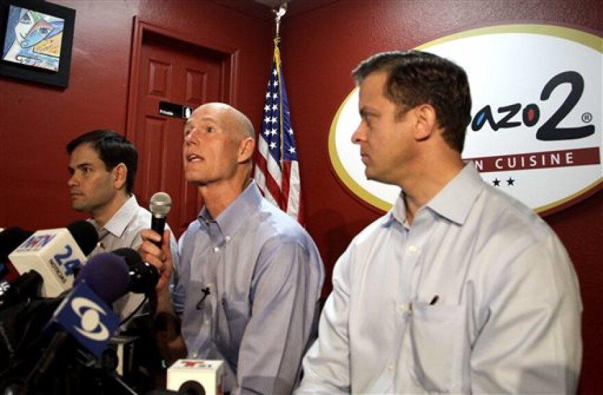 U.S. Sen. Marco Rubio, left, Florida Gov. Rick Scott and Lt. Gov. Carlos Lopez-Cantera, right, speak to the media in El Arepazo 2 restaurant in Doral, Fla., on Friday, Feb. 28, 2014.