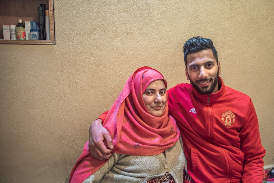 Muhammad Hammad (right), 21, who plays center-back for Real Kashmir, sits at home with his mother Mahjabeen.