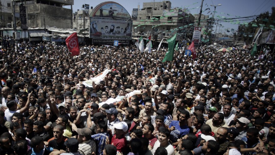Palestinian mourners carry the body of three senior commanders of the Hamas military wing in the southern Gaza Strip on Thursday, after they were killed in an Israeli airstrike. Hamas executed more than a dozen people it says were spying for Israel.