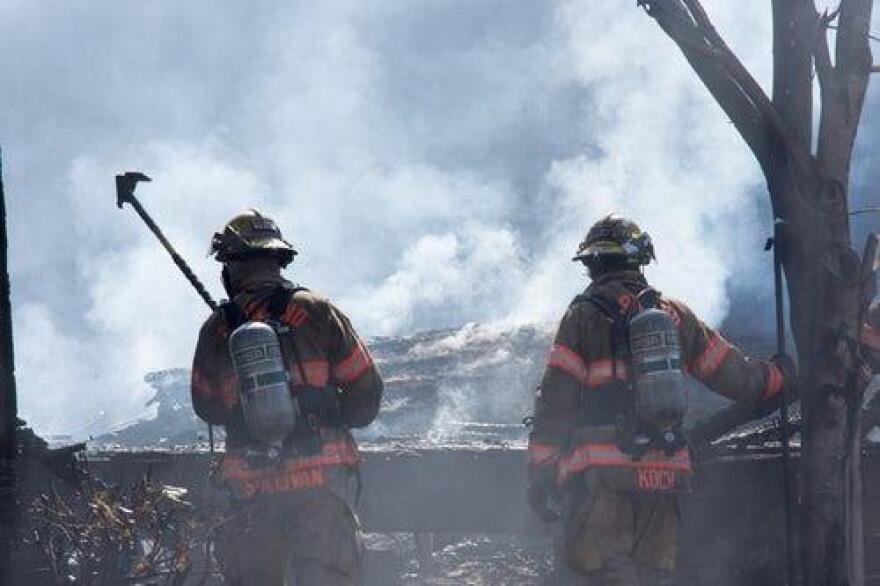 Two firefighters battle a blaze of smoke.
