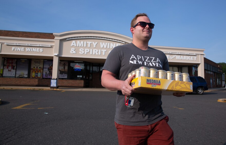 Adrián Rodriguez walks out of a liquor store in New Haven, Conn., with a 24-pack of Medalla Light.