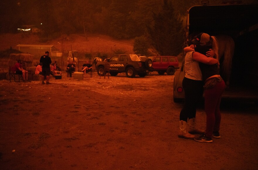 Chance Johnson hugs Sarah Hunter. The two loaded a horse into a trailer to be evacuated Wednesday in Canby, Ore.