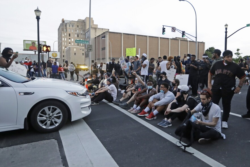 Protesters sit at an intersection during a protest over the deaths of George Floyd and Breonna Taylor in Louisville, Ky. Taylor, a black woman, was fatally shot by Louisville police in her home in March.