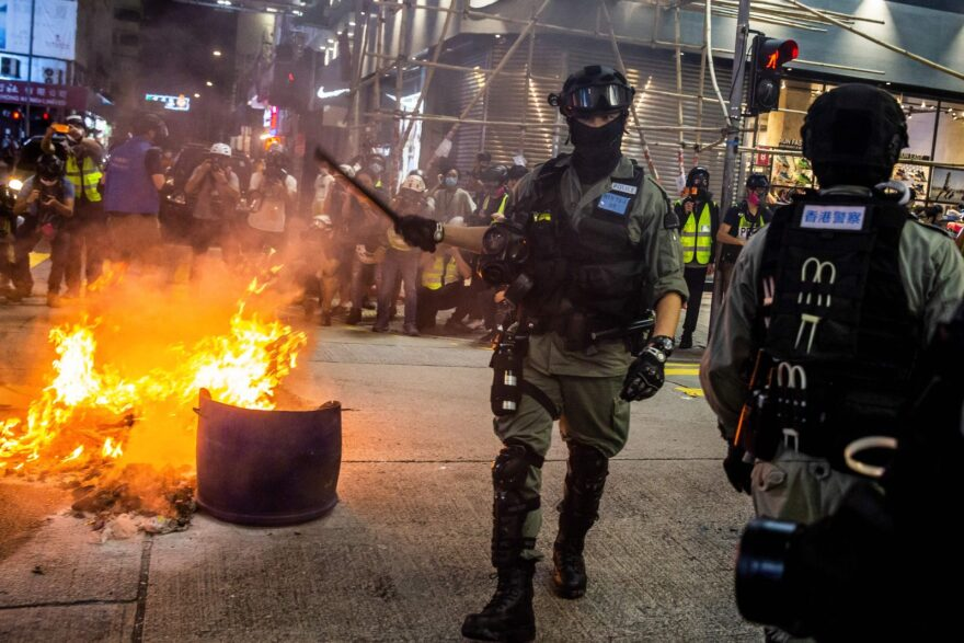 Police clear a road around a fire that was lit during a pro-democracy protest in the Mong Kok district of Hong Kong. Antigovernment demonstrations intensified this week.