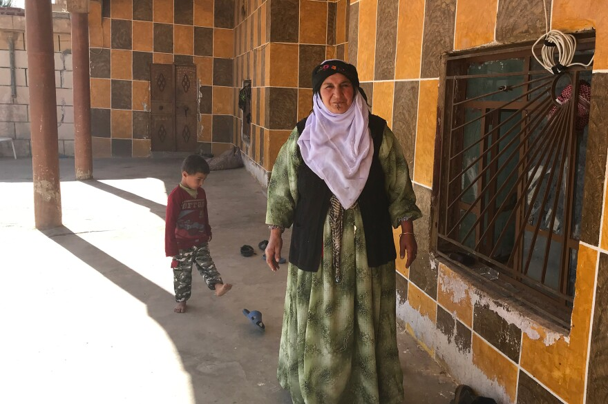 Zahura Sinan with a grandchild. She and her son's family have taken care of almost 150 Yazidi women and children rescued from ISIS.