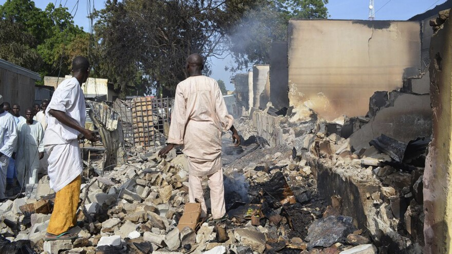 Men walk amid rubble after Boko Haram militants raided the town of Benisheik in northeast Nigeria, on Sept. 19. The Islamist group has been waging an insurgency in northern and central Nigeria for the past four years and was recently placed on the U.S. list of terrorist groups.