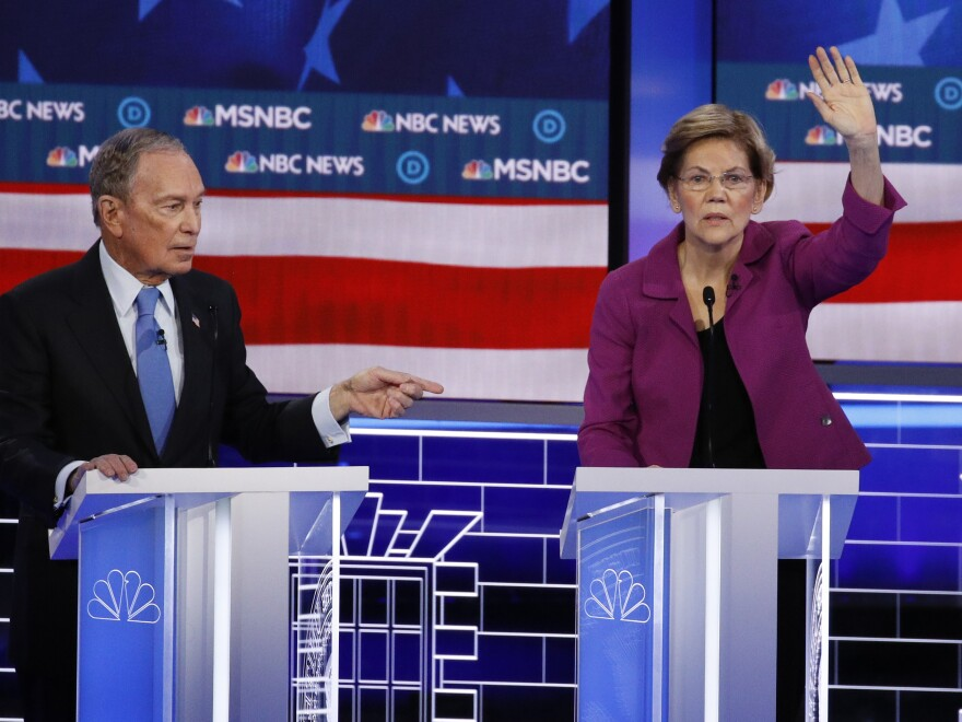 Sen. Elizabeth Warren, D-Mass., gestures during the debate as former New York City Mayor Michael Bloomberg looks on.