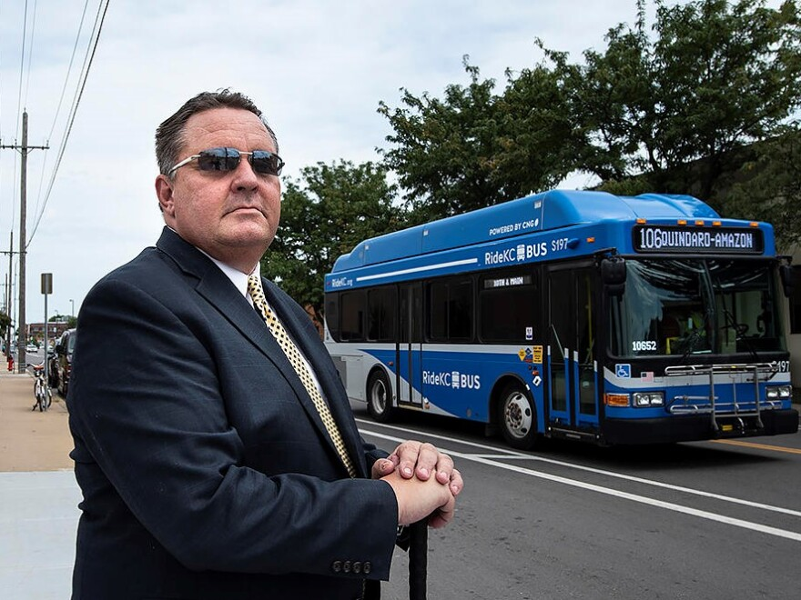 CEO of KCATA, Robbie Makinen stands in the foreground with a bus passing by behind him