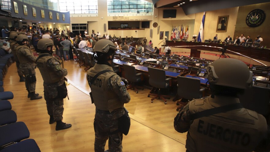 Police and army soldiers, carrying rifles and dressed in battle fatigues, entered the parliament building to show support for President Nayib Bukele's $109 million loan plan to better equip them.