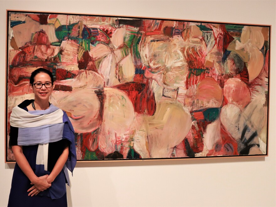A woman, curator Joanna Robotham, stands to the right of a vibrant abstract painting with red, green, and tan hues.