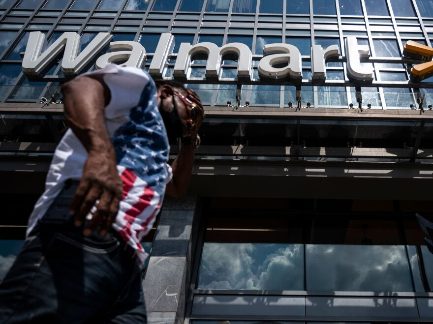 "A man walks past a Walmart store in Washington, D.C. on July 15. Walmart said it was ""confident"" that its joint deal with Microsoft would satisfy both TikTok users and U.S. government regulators."