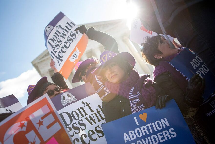 Lara Chelian (center) and her mother, Renee Chelian, both abortion providers from Michigan, hold signs in front of the U.S. Supreme Court in Washington, D.C., as the justices her arguments in Whole Woman's Health v. Hellerstedt last year.