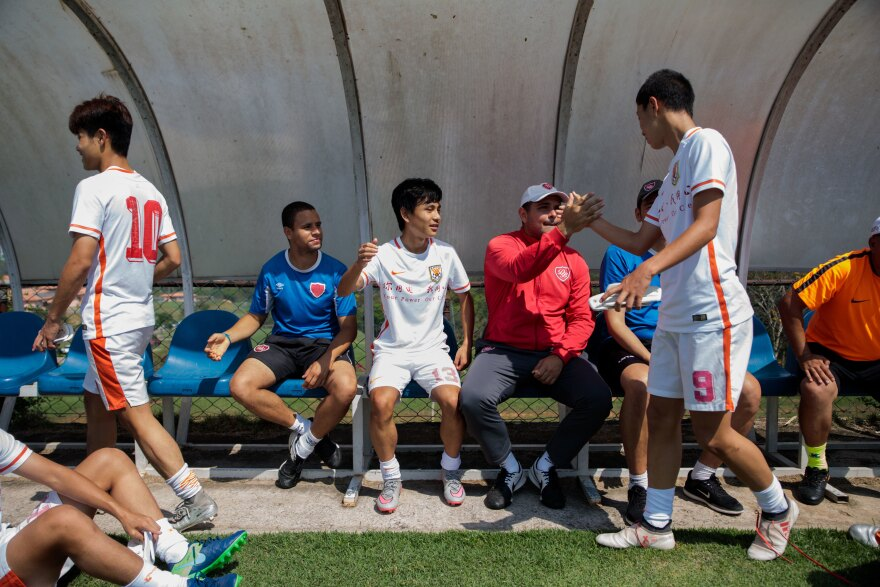 Chinese soccer players shake hands with coach Leonardo Galbes and other instructors after practice.