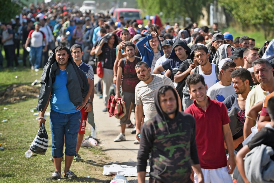 Refugees and other migrants wait to board buses at Tovarnik railway station in Croatia after crossing from Serbia on Friday. Officials say they were forced to close eight road border crossings Thursday after thousands of people entered the country when Hungary fenced off its border with Serbia earlier this week.