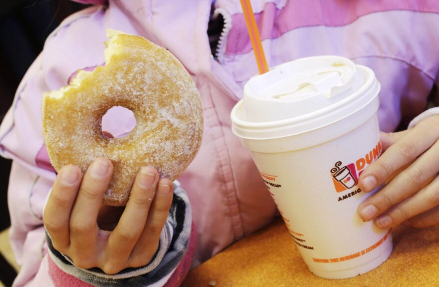 In this 2013 file photo, a girl holds a beverage, served in a foam cup, and a doughnut at a Dunkin' Donuts. (Mark Lennihan/AP)