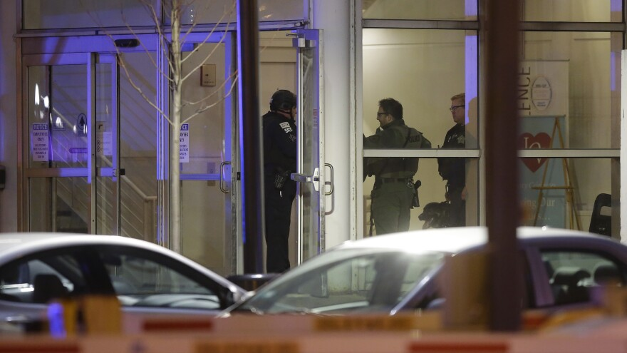 Police officers stand at one of the entrances to Mercy Hospital in Chicago on Monday after a gunman shot multiple people there.