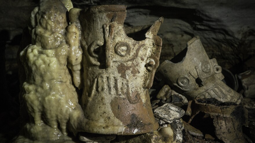 The water drip over hundreds of years has resulted in the concretion of some of the objects, including this incense burner in the shape of Mayan rain God Tlaloc.