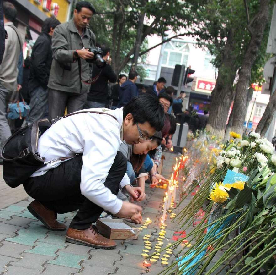 Chinese mourners placed flowers and lit candles at the scene of an attack last week that killed 39 people in the northwestern Chinese city of Urumqi. When people used social media to call for a protest, authorities tried to break up the gathering.