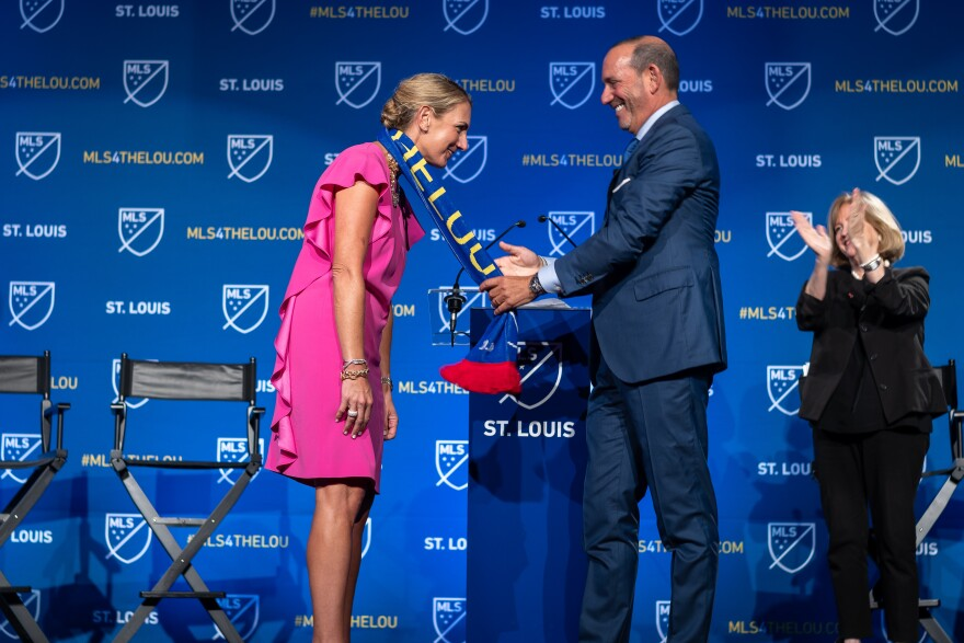 "Major League Soccer Commissioner Don Garber drapes an MLS scarf that reads ""St. Louis"" over Carolyn Kindle Betz, who leads the ownership group for St. Louis' new professional soccer team. Tuesday, Aug. 20, 2019"