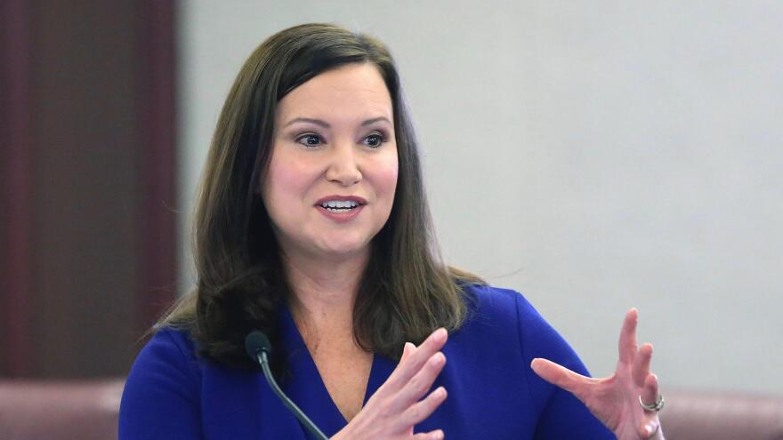 Woman speaks at microphone, gesturing with her hands.