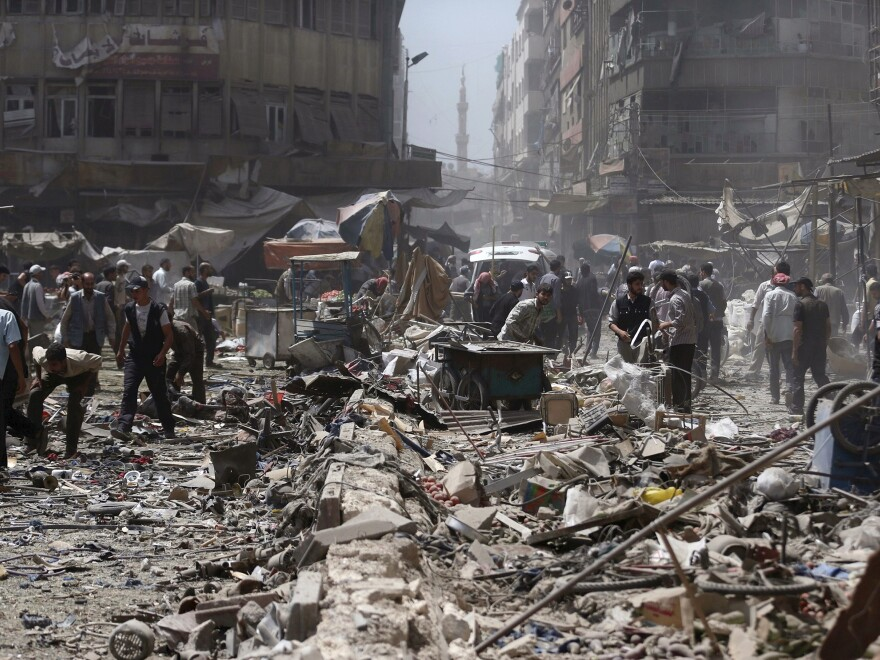 People inspect a site hit by what activists said were air strikes by forces loyal to Syria's President Bashar al-Assad on a marketplace in the Douma neighborhood of Damascus, on Sunday.