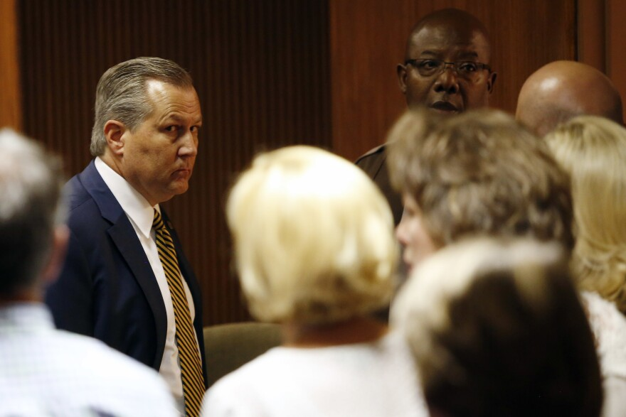 Mike Hubbard looks at family and friends sitting in the courtroom as deputies wait to take Hubbard into custody on Friday, in Opelika, Ala.