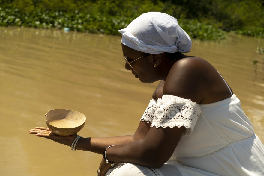 During a visit to Suriname, Peggy Bouva pours almond syrup from a dried gourd as part of a prayer for Philida, Johanna and Rosalina Bouva, three ancestors enslaved by the Dutch. Bouva spent two years researching her family's history together with Dutch radio producer Maartje Duin, whose ancestor held stock in the plantation where Bouva's relatives where enslaved.