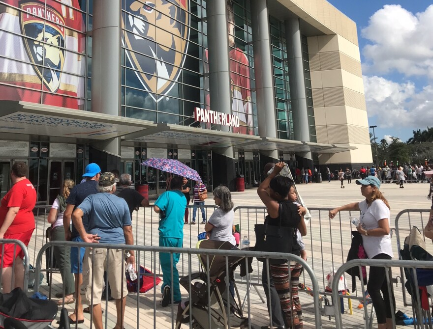 On Tuesday, many people brought umbrellas to beat the heat while waiting hours in line for disaster food stamps at the BB&T Center in Sunrise.