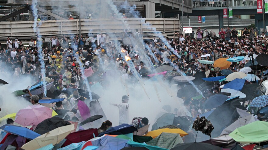 Riot police launch tear gas into a crowd of thousands of protesters outside the government headquarters in Hong Kong Sunday. Police warned of further measures as they tried to clear the streets.