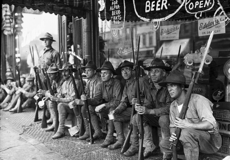 Row of armed National Guard sitting in front of a storefront during the race riots in Chicago, Illinois, 1919.