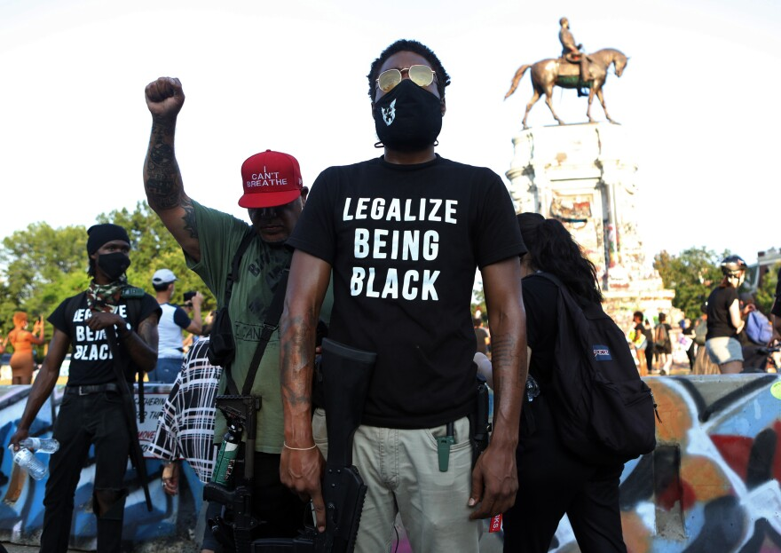 Armed protester and poet who goes by the pen name Ray Rosetta attends a demonstration at the Lee monument. Rosetta has teamed up with other local Black gun owners, many of whom are also now doing stints to safeguard the protest site at the Lee statue.