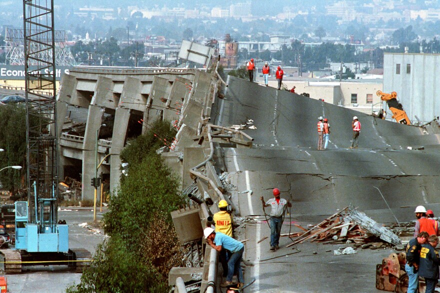 Workers check the damage to Interstate 880 in Oakland. The San Francisco-Oakland Bay Bridge collapsed during the Loma Prieta earthquake on Oct. 17, 1989.