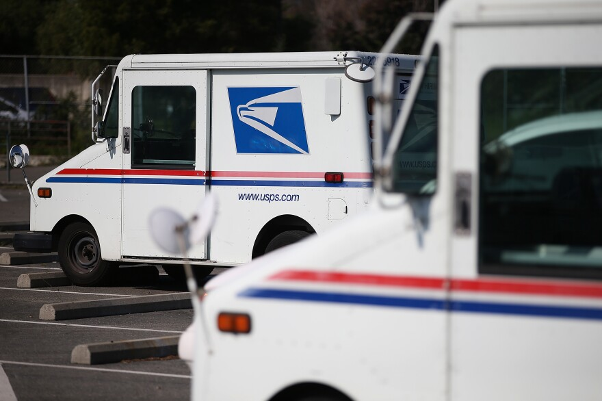 U.S. Postal Service mail vehicles sit in a parking lot at a mail distribution center on February 18, 2015 in San Francisco, Calif.