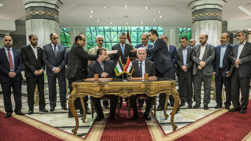 Senior Hamas leader Saleh al-Arouri (left) sits next to Fatah's Azzam al-Ahmad as they sign a reconciliation deal in Cairo on Thursday. Under the agreement, Hamas would cede control of the Gaza Strip to the Fatah-led Palestinian Authority by Dec. 1.