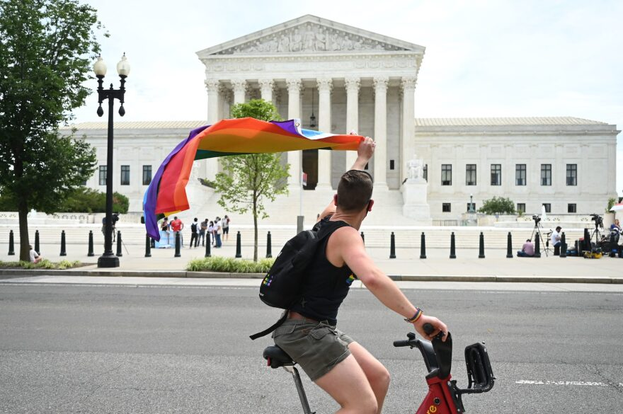 A man waves a rainbow flag as he rides by the US Supreme Court that released a decision that says federal law protects LGBTQ workers from discrimination on June 15, 2020 in Washington,DC. (JIM WATSON/AFP via Getty Images)