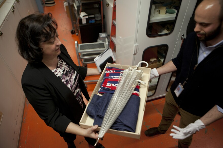 Valeska Hilbig (left), deputy director of communications and marketing at the National Museum of American History, passes along clothing that represents the spirit of campaigning in the '70s to curator Jon Grinspan.
