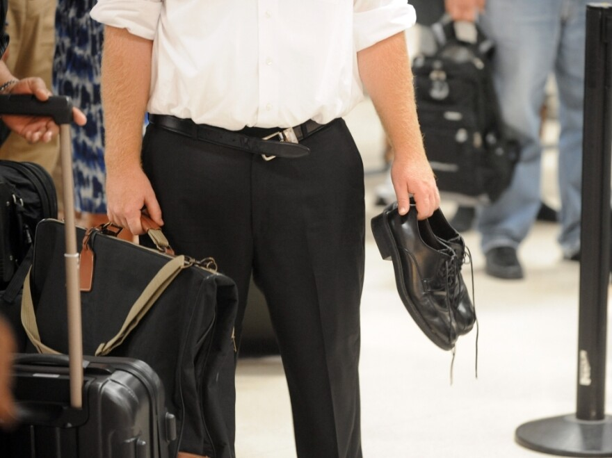 An experienced airline passenger holds his  shoes and has an unloosened belt while waiting to go through the TSA  security checkpoint at Hartsfield-Jackson Atlanta International  Airport last month.