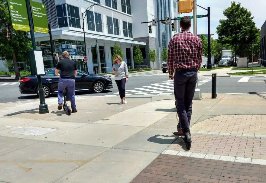 People ride scooters on a sidewalk in uptown Charlotte at lunch hour in June.