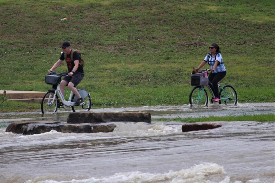 Cyclists make their way through the water on Sunday, May 25 at Padre Park.