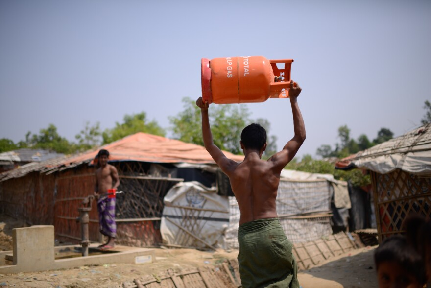A Rohingya refugee carries a gas cylinder back to his shelter in the Balukali refugee camp. The U.N. refugee agency, along with other aid organizations, has launched a program to replace wood cooking fires with gas stoves.