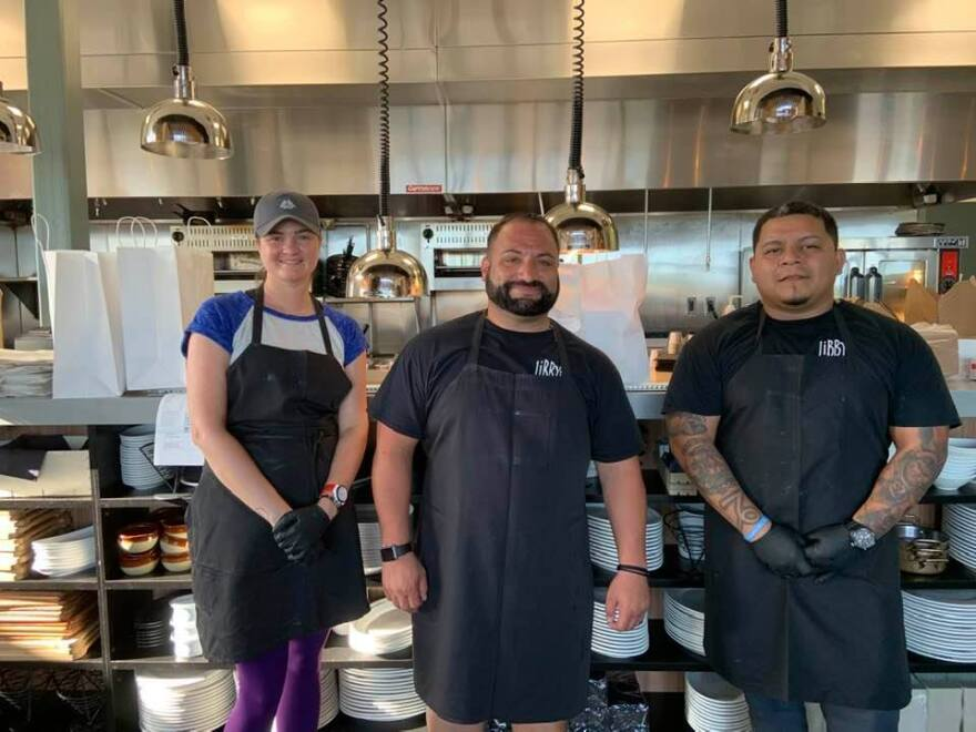 A woman and two men stand in front of a restaurant kitchen.