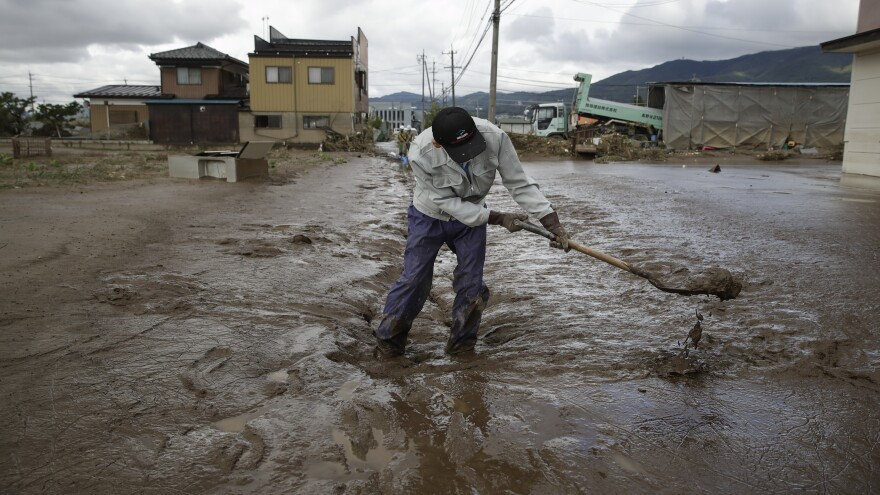 A man uses a shovel to scoop mud Tuesday in a neighborhood devastated by Typhoon Hagibis in Nagano, Japan.