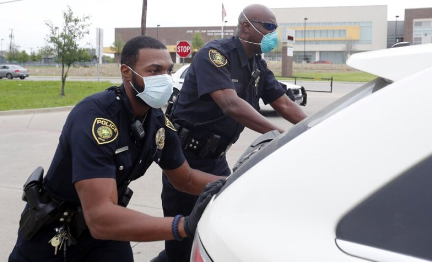 Dallas police wear masks and push a car that ran out of gas.