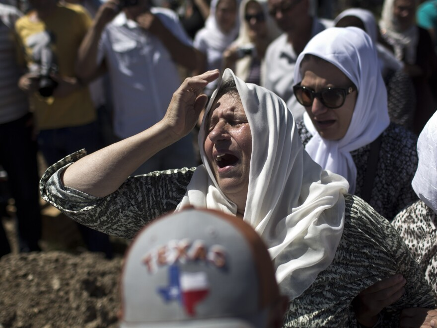 A woman cries as the remains of her son are buried during a ceremony at the Potocari memorial complex near the Bosnian town of Srebrenica last July.