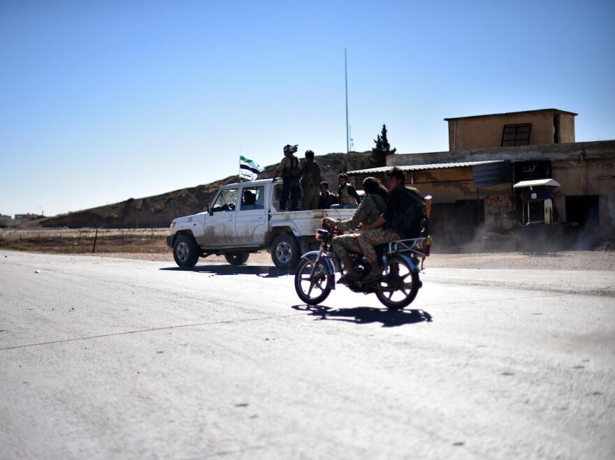 Members of the Free Syrian Army enter Dabiq village north of Aleppo on Sunday. Rebels say they have retaken Dabiq from the Islamic State.