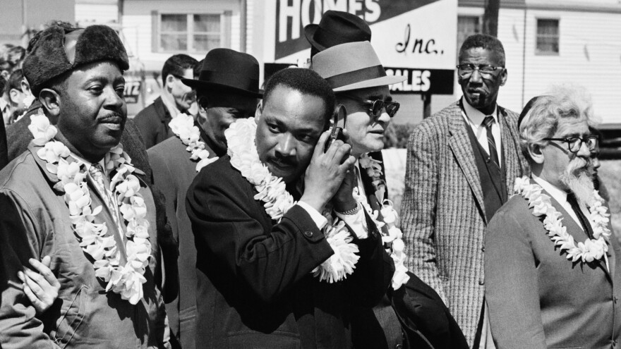 Martin Luther King, Jr. listening to a transistor radio in the front line of the third march from Selma to Montgomery, Alabama, to campaign for proper registration of black voters, March 23, 1965. Ralph Abernathy (second from left), Ralph Bunche (third from right) and Rabbi Abraham Joshua Heschel (far right) march with him.