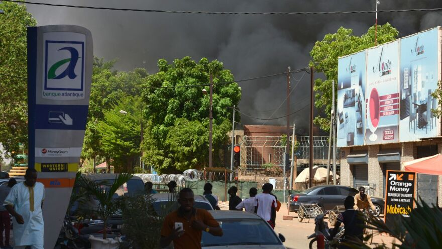 People watch as black smoke rises as the capital of Burkina Faso came under multiple attacks on Friday.