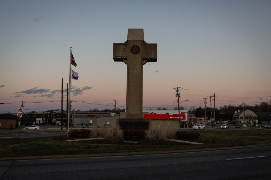 The cross sits in the median at a busy five-way intersection.